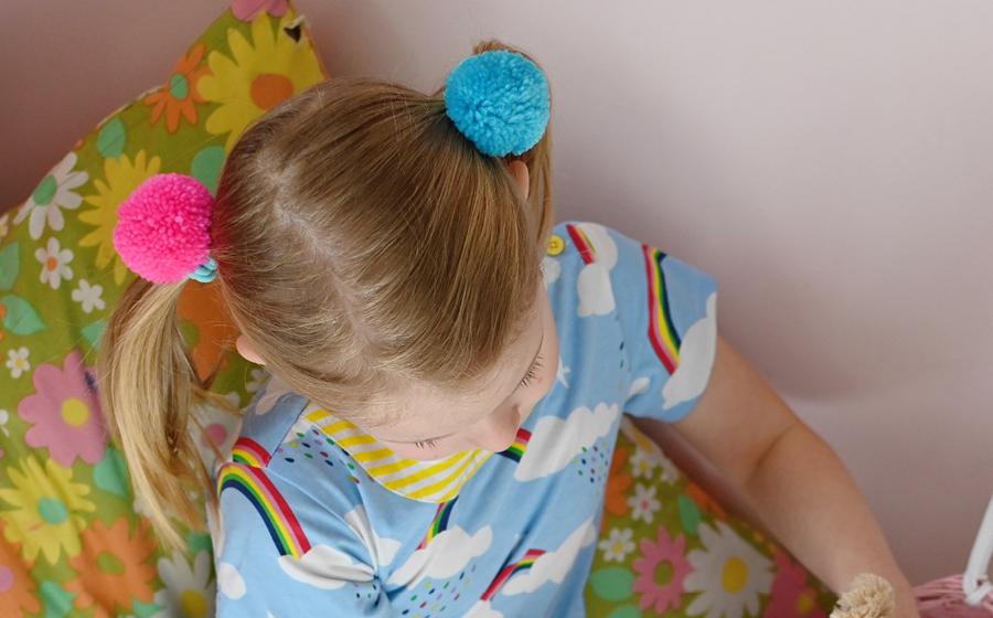 Child wearing pom pom hair bands