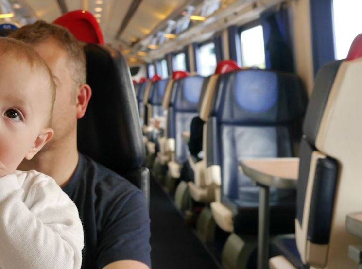 Baby sat contently on a train with his father