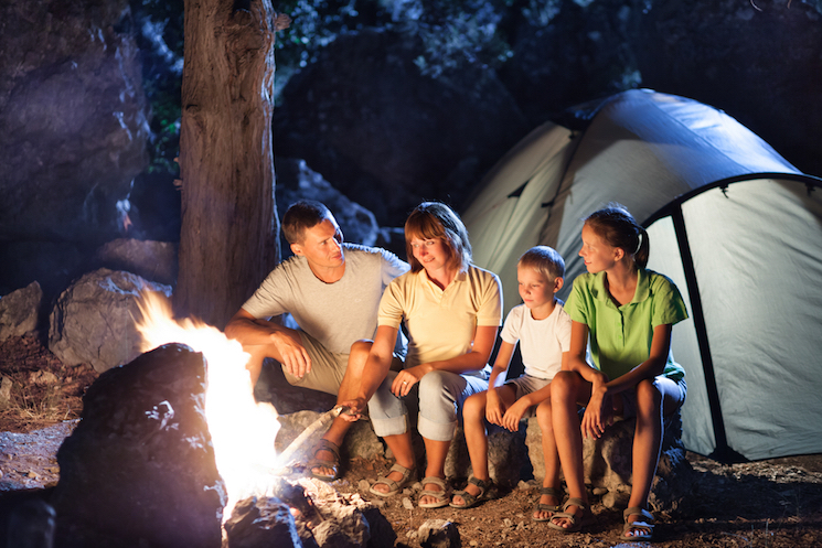 family gathered around an inviting campfire