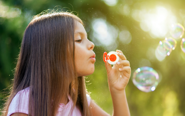 A Woman Blowing Bubbles In A Waterfront Garden Stock Image