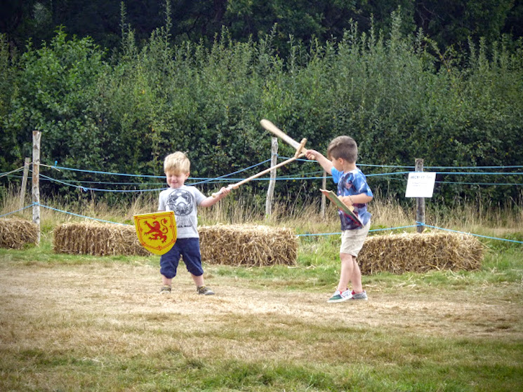 boys playing with medieval wooden swords