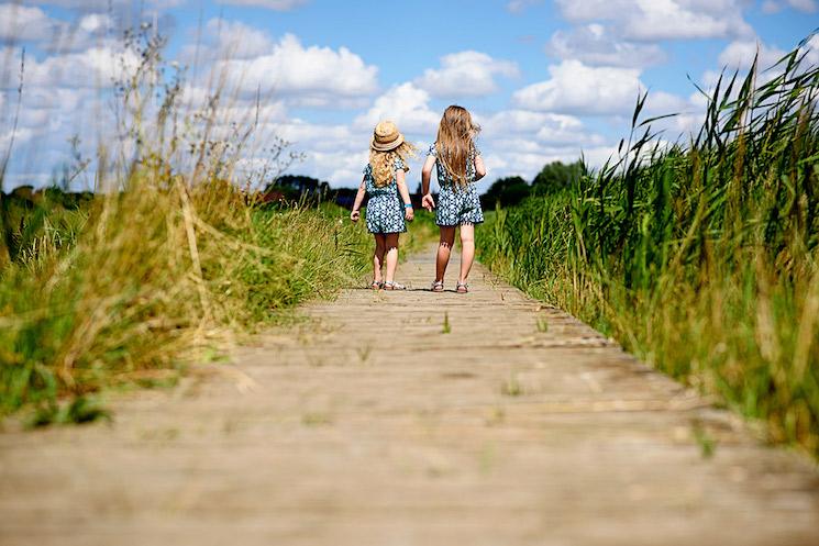 Two girls walk down wooden path through a field of long grass
