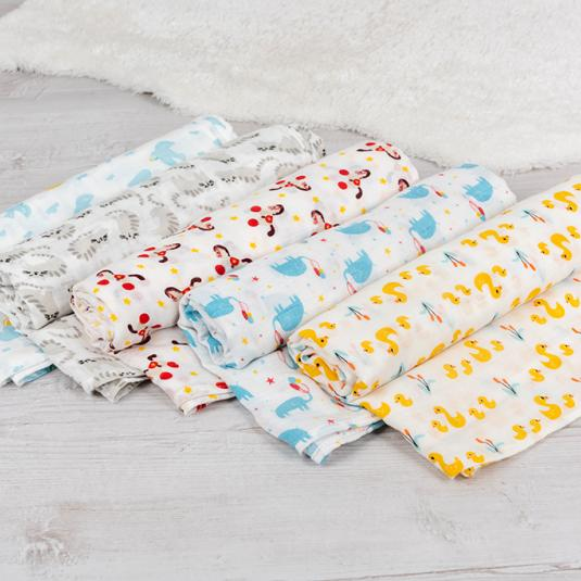 Range of white swaddling blankets with animal patterns. Elephants, ducks, horses, cats and doves.