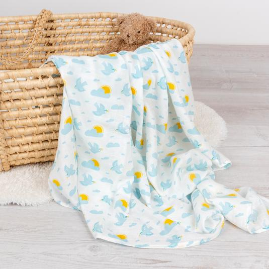 White swaddling blanket with little flying skylarks and the sun peeking out behind a cloud, in a basket.