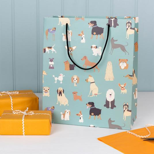 Large pale blue gift bag with cartoon dog breed pattern.
