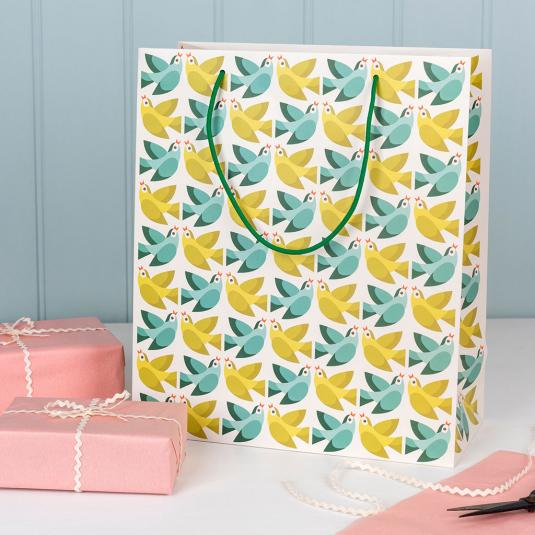 Large white gift bag with green and teal bird pattern.