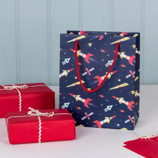 Small dark blue gift bag with space scene including rockets, satellites and planets.