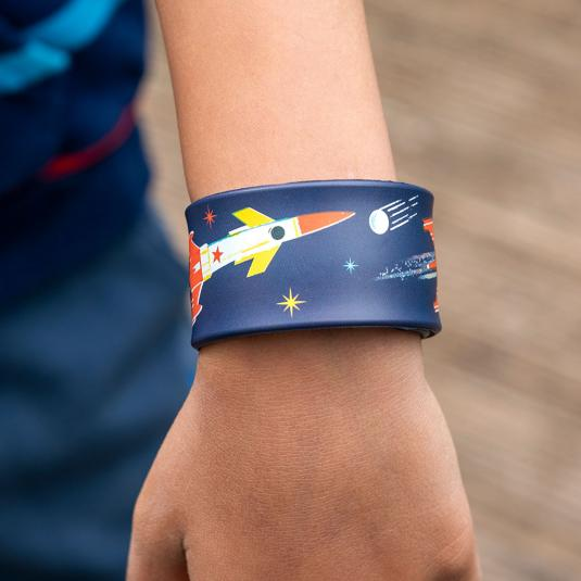 Snap band on child's wrist with space design.