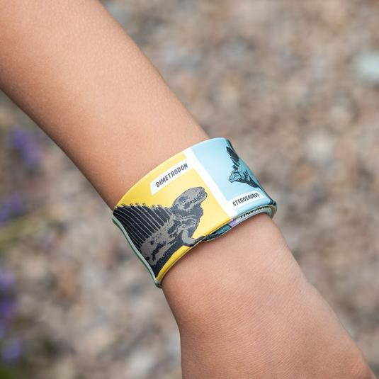 Snap band on child's wrist with dinosaur pattern.