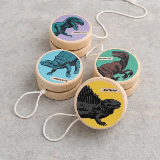Wooden yoyos with colourful dinosaurs. Tyrannosaurus, ankylosaurus, dimetrodon and velociraptor.