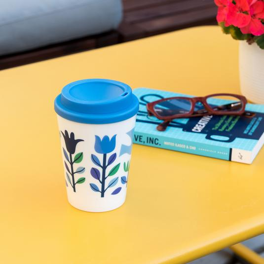 white plastic travel coffee cup with blue lid and blue floral print