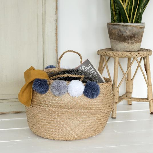 Woven belly basket home storage solution with grey pom poms