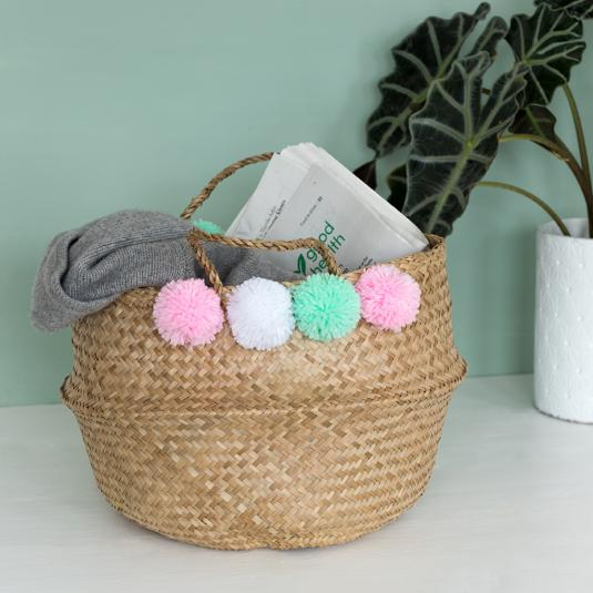 Seagrass belly basket with pastel pom poms for home storage